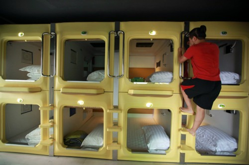 A guest climbs down a capsule in a newly opened capsule hotel in Haikou, south China's Hainan province on August 13, 2013. The capsules are the length and width of no more than a single bed and equipped with ventilating fans, flat-panel televisions and foldable tables. (Getty Images)